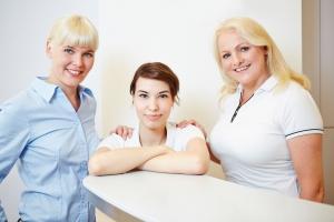 Zahnärztin mit Arzthelferin und zahnmedizinischer Fachangestellten an der Rezeption